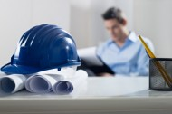 Blue hardhat sitting on plans, architect in background